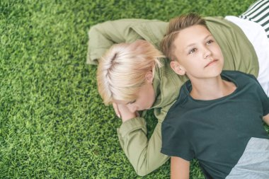top view of beautiful mother and son resting together on green lawn
