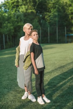 full length view of beautiful stylish mother and son standing back to back on green lawn