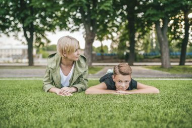 beautiful mother and son lying together on green grass
