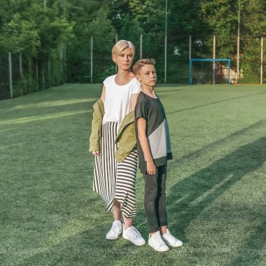 full length view of beautiful stylish mother and son looking at camera while standing together in green lawn