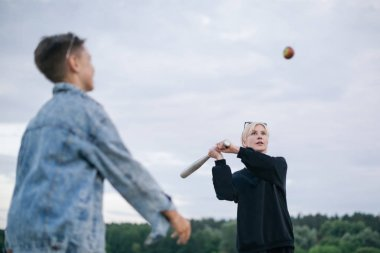selective focus of mother and son playing baseball together outdoors