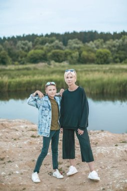beautiful stylish mother and son looking at camera while standing with baseball bat near lake