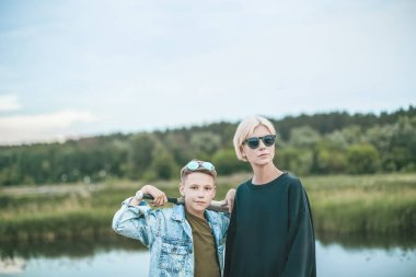 beautiful stylish mother and son standing with baseball bat near lake