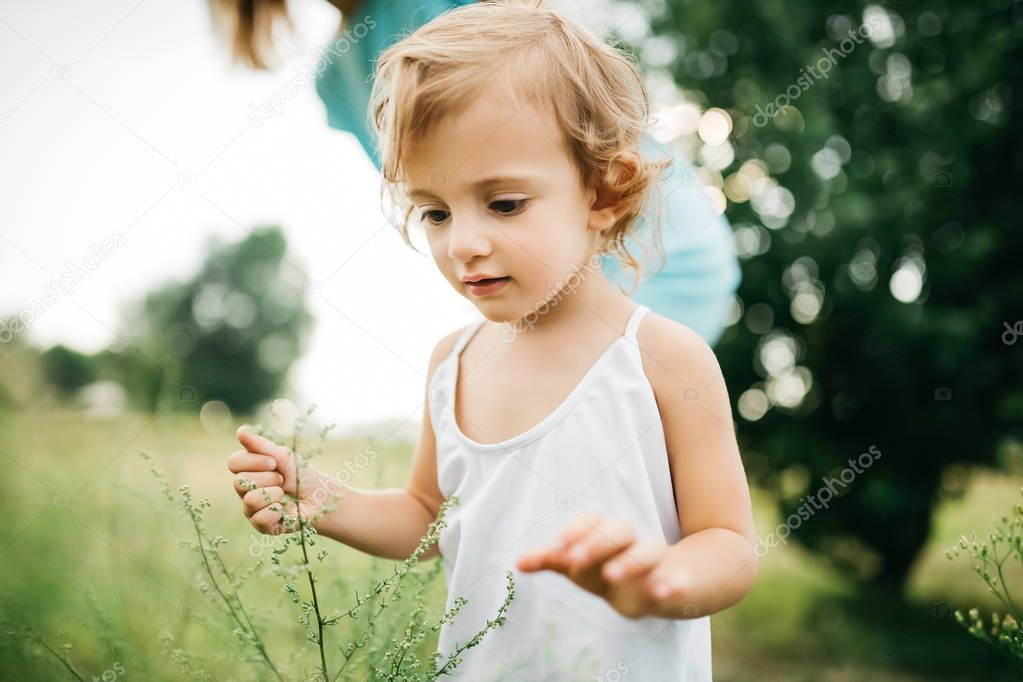 cropped image of child touching twigs in field