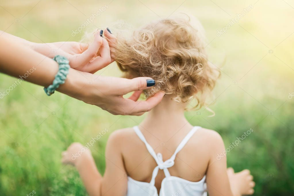 cropped image of mother touching child curly hair outdoors
