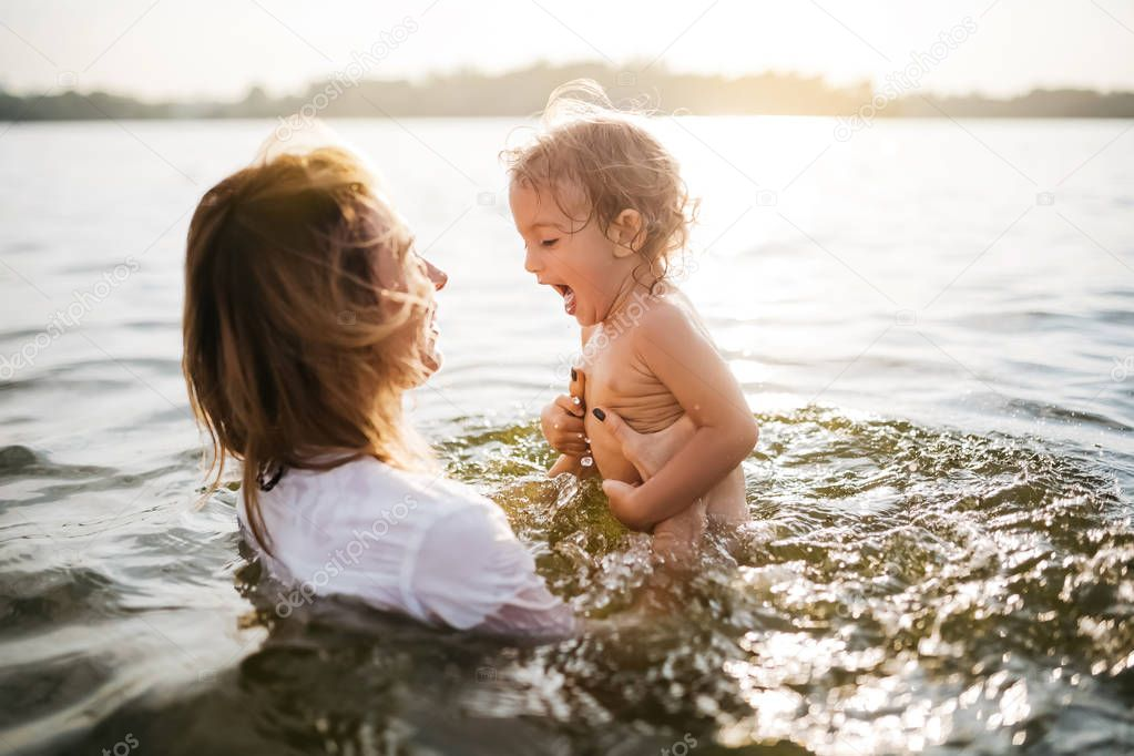 happy mother holding screaming daughter in river