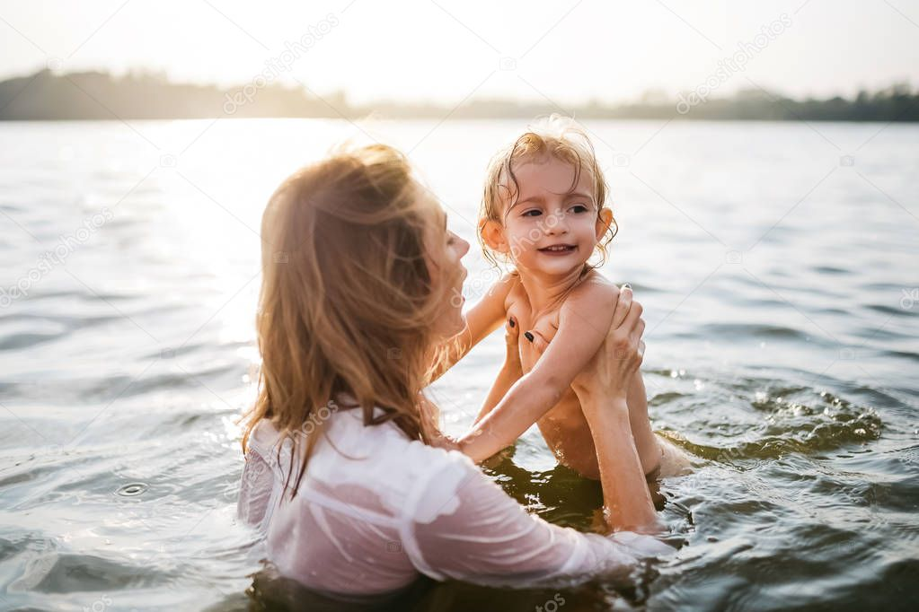 mother holding happy daughter in river during sunset