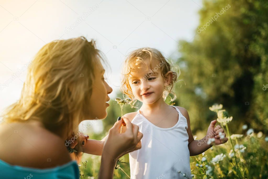 mother sniffing field flowers, smiling daughter looking at mom
