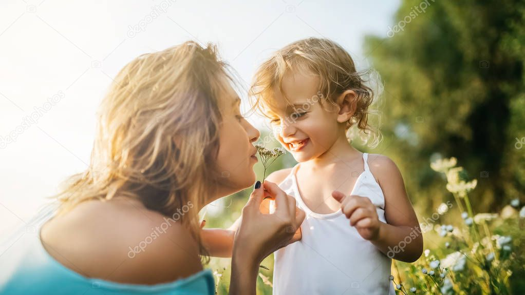 mother sniffing field flowers near daughter