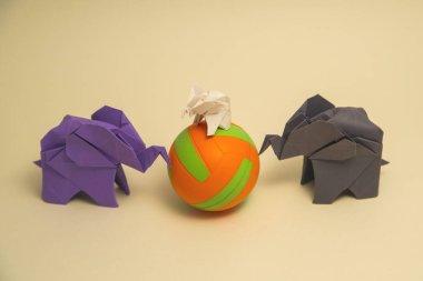 """Картина, постер, плакат, фотообои """"слоны оригами сделаны из цветной бумаги на зеленом фоне. концепция сохранения бумаги и леса. семья и детство. макет, место для копирования. море"""", артикул 393133614"""