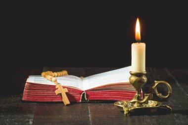 Tespih kitap ve siyah bir zemin üzerine bir mum yanan bir mum