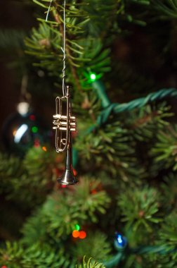 Tiny trumpet ornament decoration hangs from Christmas tree branch