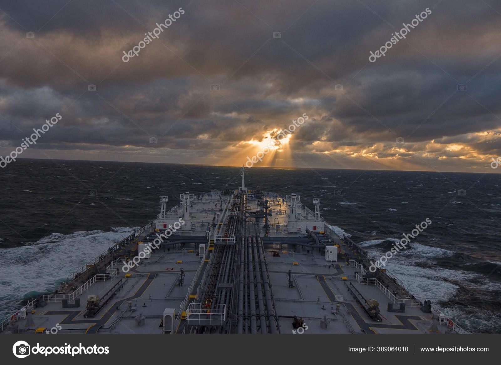 嵐の天候の日の出を背景に原油タンカーのデッキ 美しいデスクトップの