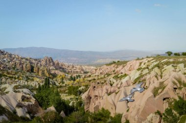aerial view of mountains and cityscape under bright blue sky in Cappadocia, Turkey