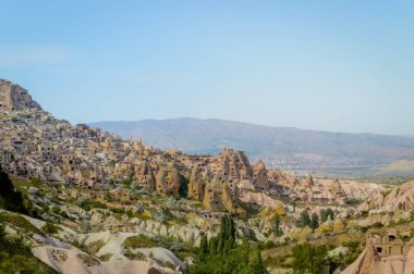 aerial view of cityscape and mountains under cloudless blue sky in Cappadocia, Turkey