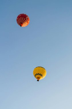 yellow and red hot air balloons flying in cloudless blue sky, Cappadocia, Turkey