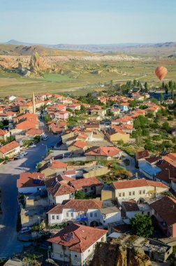 aerial view of hot air balloon flying over buildings in city, Cappadocia, Turkey
