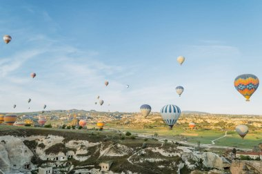 front view of colorful hot air balloons flying over city in Cappadocia, Turkey