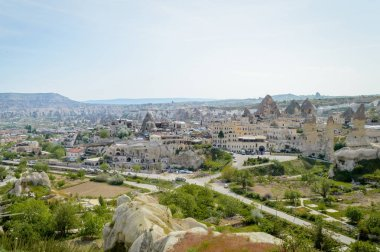 aerial view of cityscape and stone formations under cloudy blue sky, Cappadocia, Turkey