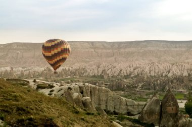 scenic view of hot air balloon flying over stone formations in valley of Cappadocia, Turkey