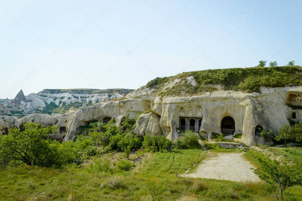 old cave dwellings in valley under blue sky, Cappadocia, Turkey