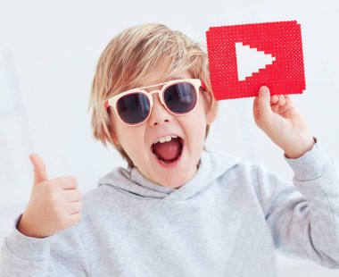 Portrait of cute happy boy, kid with play button icon and thumb up