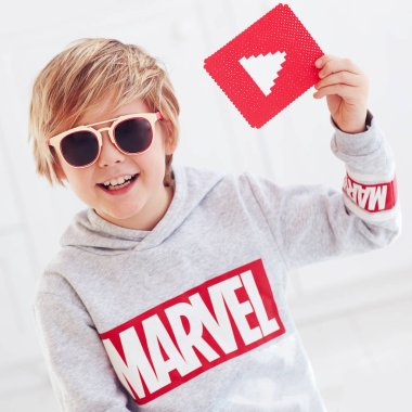Ukraine- September 30, 2018: Portrait of cute happy boy, kid with marvel logo and youtube play icon