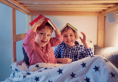 cheerful kids, brothers having fun, playing with books on the bunk bed during bedtime