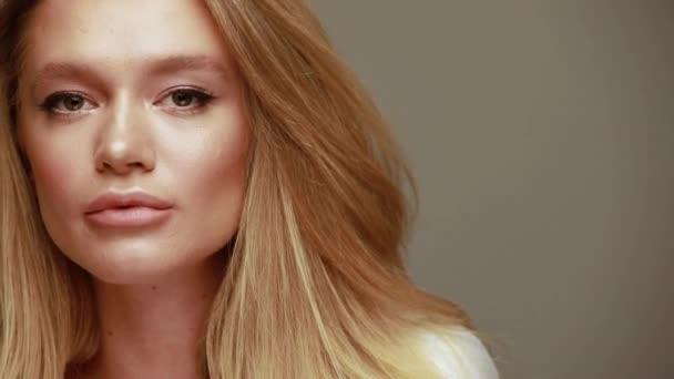 Krásná mladá žena s dlouhými blond vlasy. Blízko s pěknou ženskou tváří. Módní model s buclatými rty a dokonalým make-upem ve studiu. Krásná žena. Kosmetická koncepce. Vysoké rozlišení