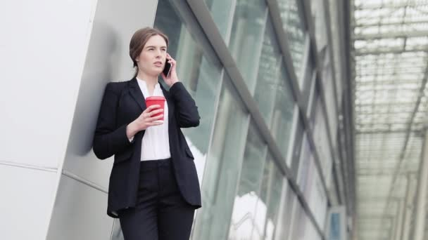 Portréja mosolygó fiatal nő beszél telefonon a nyári utcában, lassú Mo