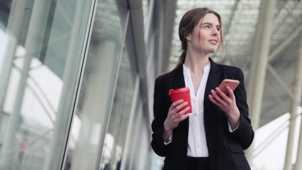 Szép fiatal Businesswoman állva a város smartphone a kezében. Látszó boldog és megelégedett. Beszélgető-ban társadalmi hálózat. Kellemes hangulat. Üvegház a háttérben.