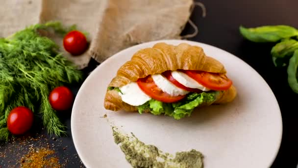 Breakfast croissant sandwich with mozzarella and tomatoes. Top view. black background with vegetables. Slow-mo