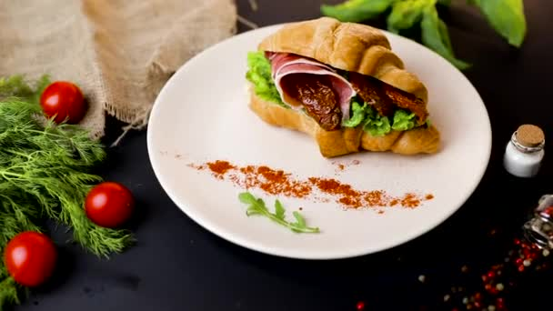 Breakfast croissant sandwich with bacon and tomatoes. Top view. black background with vegetables. Slow-mo