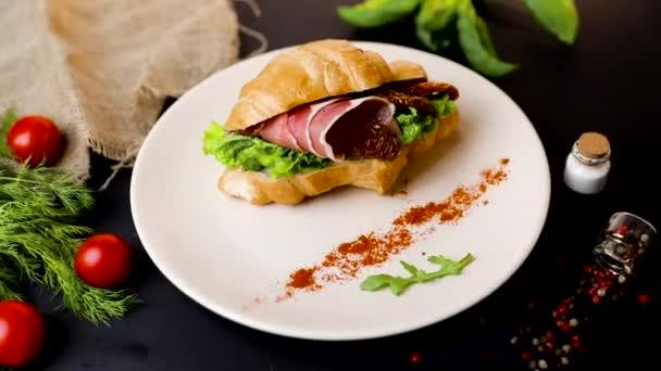 Reggeli croissant szendvics szalonnával és paradicsommal. Felülnézet. fekete háttér zöldségekkel. Lassú-Mo