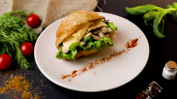 Breakfast croissant sandwich with mushrooms, tomatoes and onions. Top view. black background with vegetables. Slow-mo