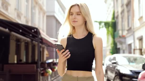 eautiful young businesswoman wearing white shirt and using modern smart phone while walking at break in the city, professional female employer typing text message on cellphone outside, slow motion