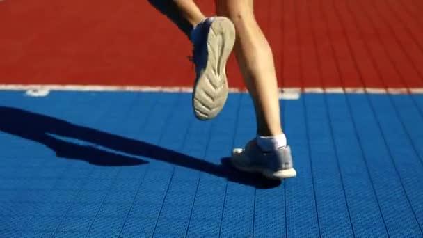 Schöne Frau auf der Straße laufen, Musik hören. Schöne Mädchen Runner helle Sportswear tragen Sportgeräte: Fitness-Tracker, Kopfhörer und Armband Joggen im Freien. Hohe Auflösung