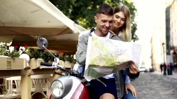 Couple with map travelers around city with motorbike scooter - Wander friends having fun on road trip in city - Travel concept with adult people on world tour - Warm filter