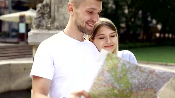 Couple With Map On Travel Vacations, Sightseeing. Happy Tourist Man And Woman In Stylish Clothes Traveling On Weekend, Walking With Map Around Streets. Tourism Concept. High Quality Image.