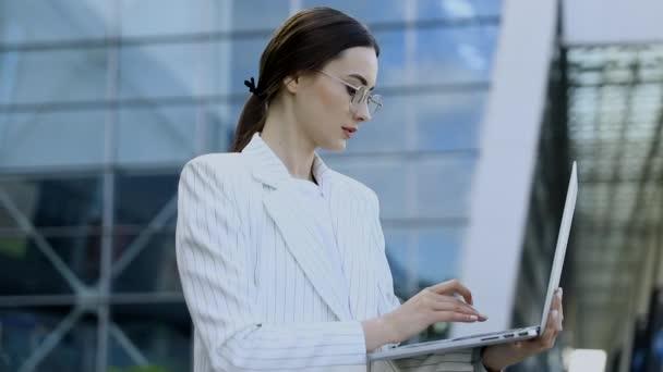 Közeli fel a fiatal szakmai üzletasszony használ neki laptop kívül, miközben dolgozik a modern üzleti központ, modern épületek a háttérben, fényfolt, film hatások, lassított