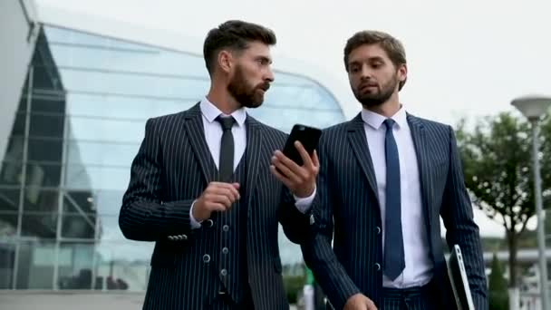 Business, technology and people concept. Image of two young businessmen communicating at meeting