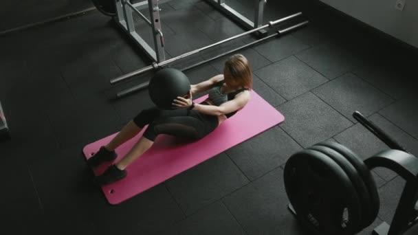 Schöne Frau in bauchfreiem Top und Sportleggings, die Bauchmuskelübungen mit Fitnessball auf der Yogamatte macht. Starkes schlankes Mädchen trainiert Bauchmuskeln im Sportverein.