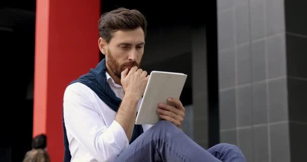 Koncentrált üzletember fehér ingben, digitális táblagéppel megoldja a munkahelyi problémákat a távolban. Szakállas fickó ül a friss levegőn és nézi a képernyőn a modern szerkentyű.