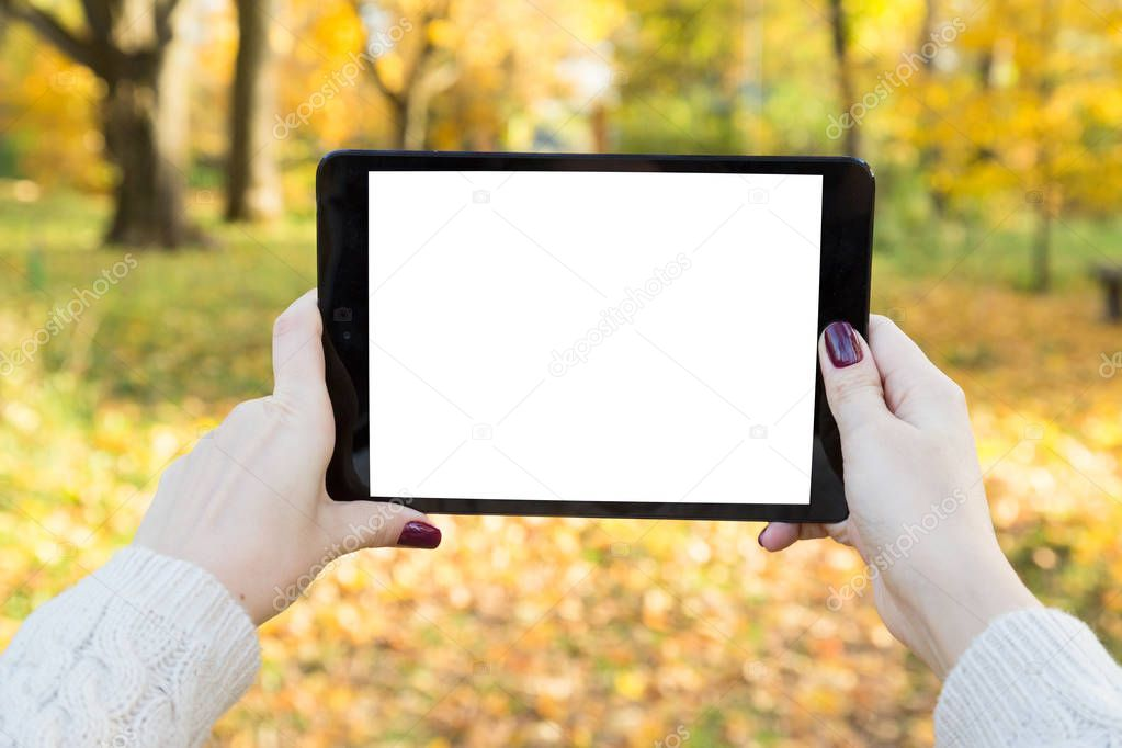 Girl takes a picture of autumn park on the tablet