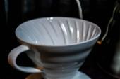 Fehér tölcsér Pourover a fekete háttér, a kávé elkészítése alternatív módszer szerint. Munka a barista kávézóban.