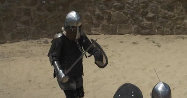 The confrontation of men and women in the arena in armor with swords