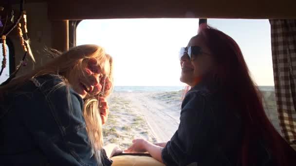 zwei Mädchen lachen vor dem Hintergrund des Autotrailers, hinter dem die Küste