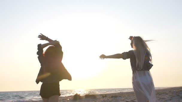 tanec na pláži dvou mladých sexy žen oblečených v Bohově stylu v záři slunce nad mořem