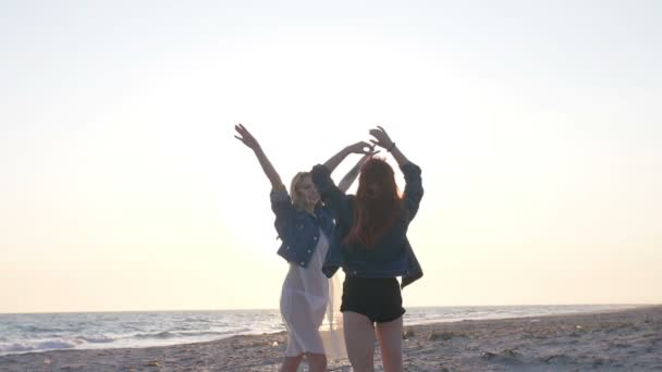 dvě mladé sexy ženy oblečené ve stylu bohémské radosti a baví se v paprscích západu slunce nad mořem na pláži