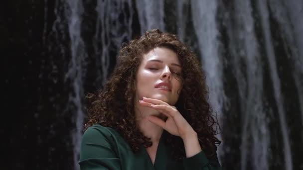 krásná mladá žena se kudrnatými vlasy užívajícími svěžest vodopádu